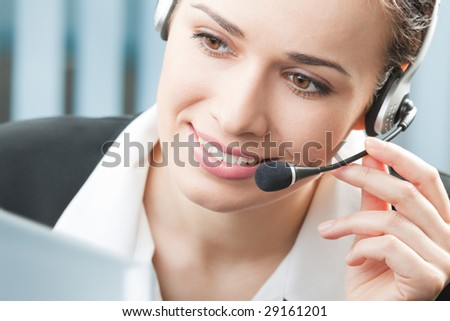 Support phone operator in headset with computer at workplace - stock photo