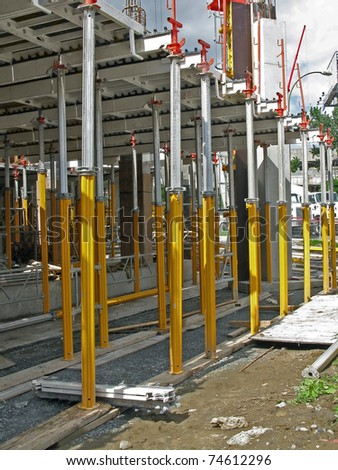 "support posts holding cement floor slabs on construction site,"" structural support"" - stock photo"