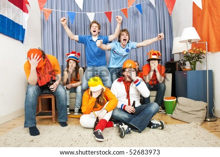 Supporters from the opposite team cheering in a mixed group of football fans - stock photo