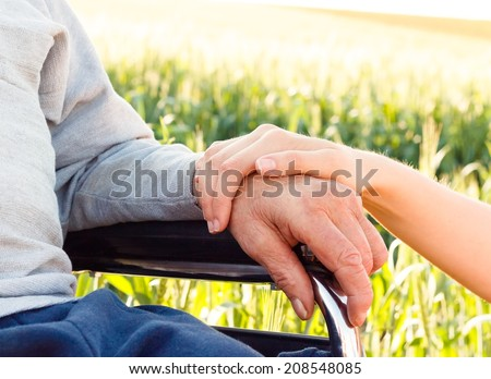 Supporting hand for grandfather with Alzheimer's disease. - stock photo