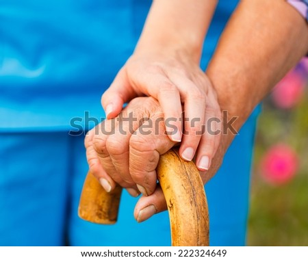 Supporting hand from doctor for elderly with parkinson's disease. - stock photo