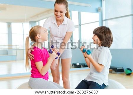 Supporting kids in training. Cheerful instructor helping children with exercising in health club  - stock photo