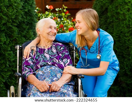 Supporting young doctor with elderly patient at the nursing home. - stock photo
