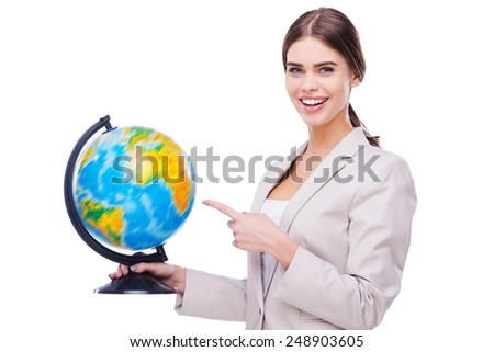Supporting your business all around the world. Beautiful young women holding globe and pointing on it while standing against white background