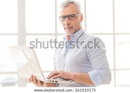 Supporting your business. Confident grey hair senior man in shirt working on laptop and looking at camera while standing in front of the window - stock photo