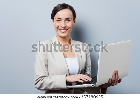 Supporting your business. Confident young businesswoman holding laptop and smiling while standing against grey background - stock photo