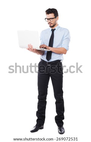 Supporting your business. Full length of handsome young man in shirt and tie working on laptop while standing against white background - stock photo