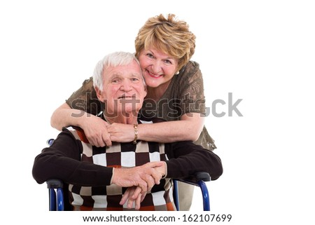 supportive elderly wife hugging handicapped husband isolated on white - stock photo