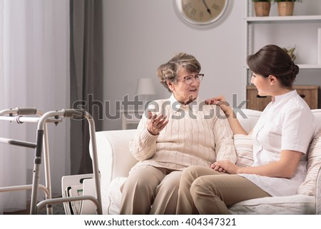 Supportive young carer sitting with older patient - stock photo