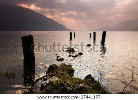 Supports for old jetty lead out into Loch Lomond - stock photo