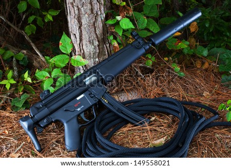 Suppressed assault rifle that is at a forest edge - stock photo
