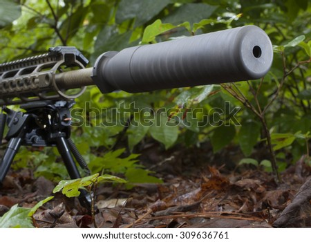 Suppressor mounted on a rifle that is in the woods