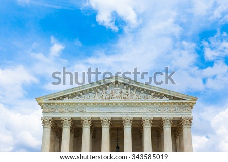 Supreme Court Building with blue sky and white puffy clouds close-up - stock photo