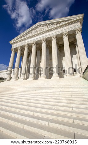 Supreme Court of the United States in Washington D,C. Blue sky behind. - stock photo