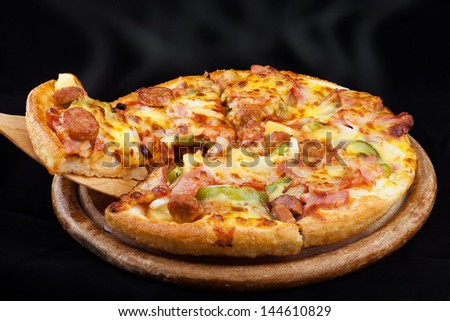 Supreme Hot Pizza lifted with black blackground - stock photo