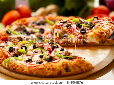 Supreme pizza lifted slice - stock photo