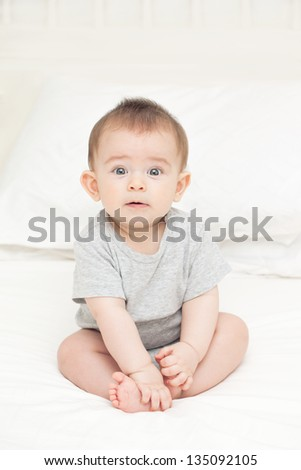 Suprised funny baby boy sitting on the bed - stock photo