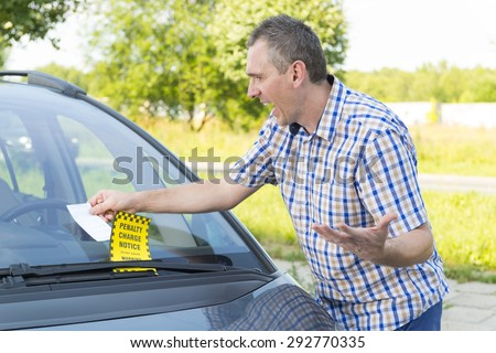 Suprised man looking on parking ticket placed under windshield wiper - stock photo
