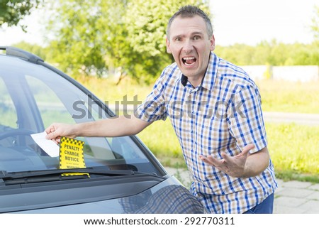 Suprised screaming man looking on parking ticket placed under windshield wiper - stock photo