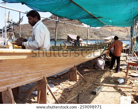 SUR,OMAN - DEC 30 2007:Traditional Omani wood boats (Dhows) builders in a workshop in Sure Fishermen village Sur, Oman. It's one of the most famous cities in the Persian Gulf in building wooden boats. - stock photo