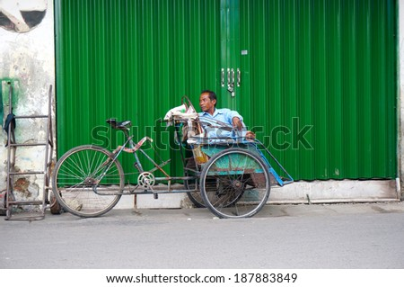 SURABAYA-APRIL 10: An unidentified rickshaw rider is resting on a street in Surabaya. rickshaw is the cheapest transportation in Surabaya, Indonesia on April 10 2014                               - stock photo