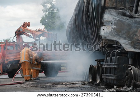 SURATTHANI THAILAND- AUG 17: Police firefighter rescuers helped extinguish a burning tractor trailer trucks horn pure alcohol on Aug 17,2014 in suratthani province,thailand