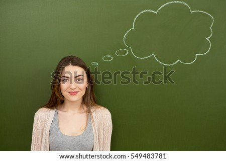 Sure about her choice. Gorgeous young woman smiling joyfully posing in front of a chalkboard with a thought bubble drawn on it copyspace dreaming dream think smart people feeling emotions wish concept