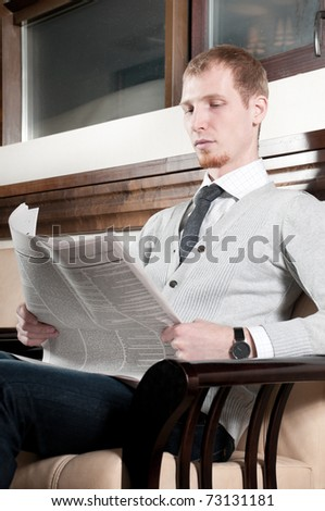 Sure young business man in office rest room  interior with fresh newspaper - stock photo