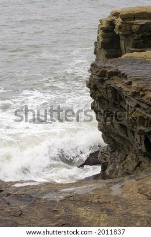 Surf against rocks - stock photo