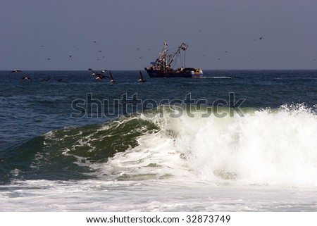 Surf and a trawler in the background - stock photo