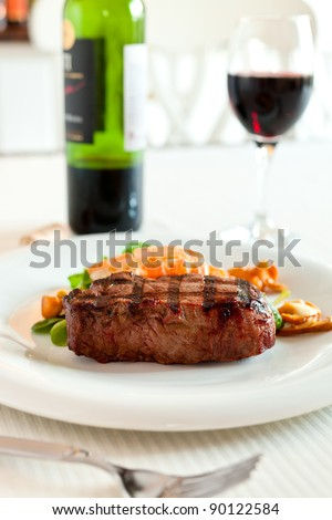 Surf and turf meal with fresh scampi and steak. Red wine in the background and shallow depth of field. - stock photo