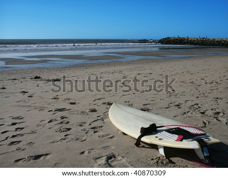 surf board on the sand of a surfer beach - stock photo