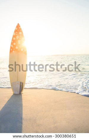 surf board standing on the sand at the beach - stock photo