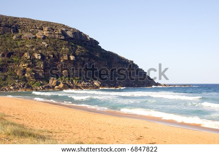 Surf crashes onto beach on a beautiful blue sky day with large cliff headland or point. Typical of the New South Wales coastline, Australia - stock photo