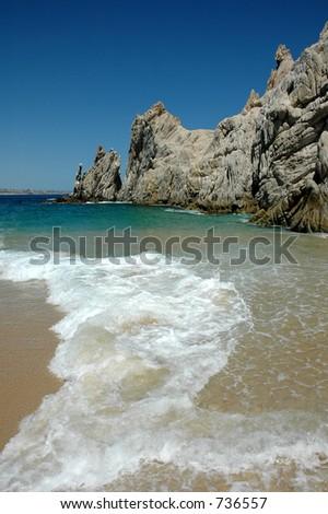 surf on beach with rocks - stock photo