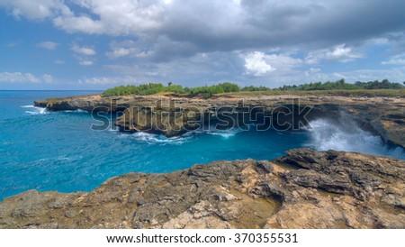 Surf on the rocks near the island of Lembongan near Bali, Indonesia - stock photo