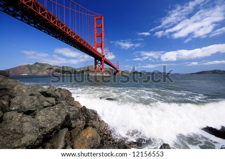 Surf splashes over rocks under Golden Gate Bridge as seen from the Fort Point beach.