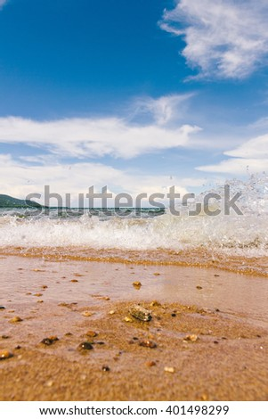 surf waves run ashore on a background of blue sky