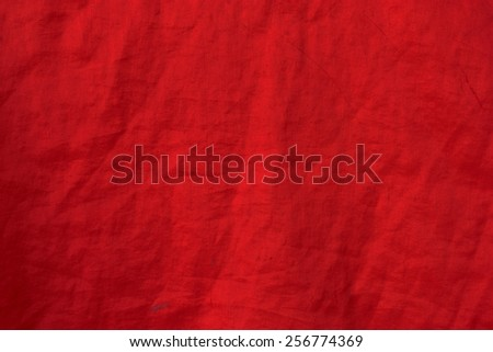 Surface close-up of red cloth with wrinkles, stains. - stock photo