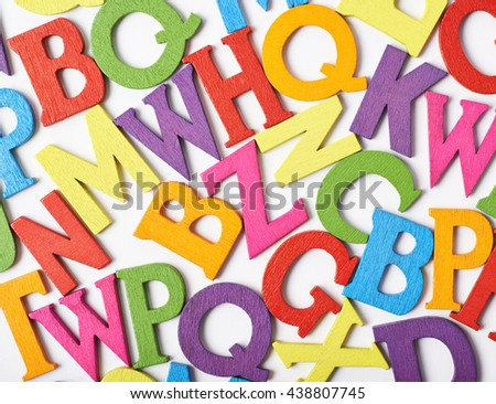 Surface covered with colorful wooden letters as an abstract background composition