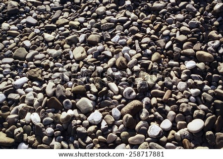 Surface covered with gray stones rounded pebbles closeup