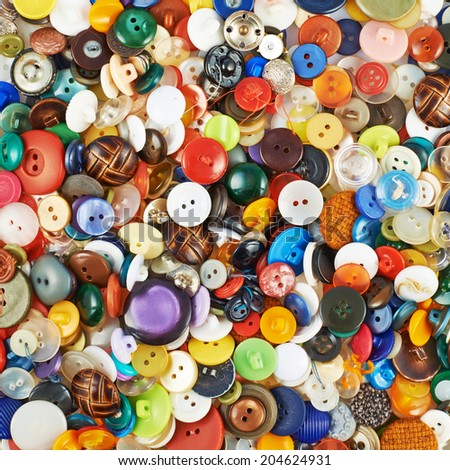 Surface covered with multiple colorful buttons of all kinds and shapes as a background texture composition - stock photo