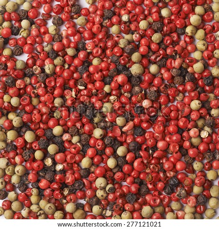 Surface covered with multiple red, black and green pepper seeds as a background texture composition - stock photo