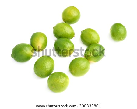 Surface covered with multiple ripe green limes, composition isolated over the white background - stock photo