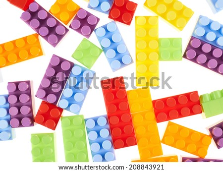 Surface covered with the colorful toy construction bricks over the white, as a background compostion - stock photo