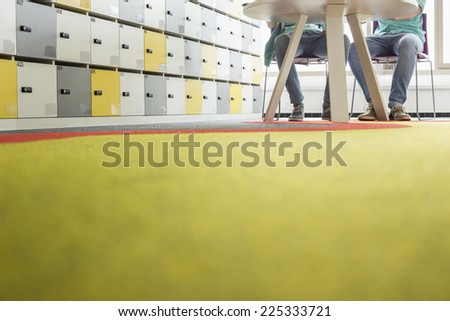 Surface level of businessmen at table in creative office - stock photo