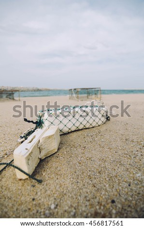 surface level of white fish buoy on sandy beach over crab pot background.focus on white buoy.shallow depth of field - stock photo