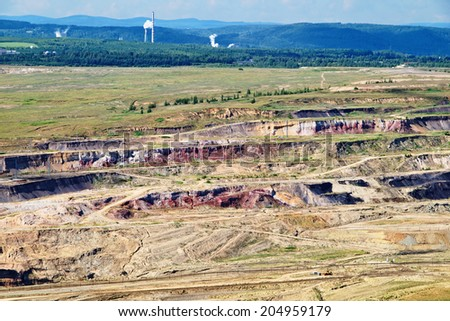 Surface mine with red minerals and brown coal, in the background smoking factory chimneys, forest and mountains, view from above - stock photo