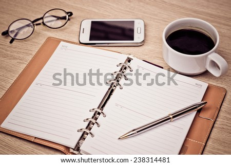 surface of a wooden table with notebook, smartphone, eye glasses, and pen - stock photo
