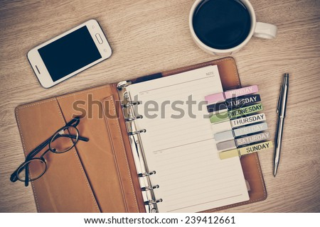 surface of a wooden table with notebook, smartphone, eye glasses, and pen, top view - stock photo